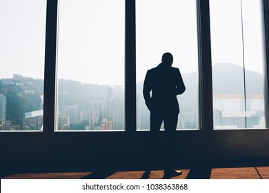 Back view of businessman in elegant suit standing indoors in loft interior.Male entrepreneur dressed in formal wear looking out of window enjoying scenery and thinking on building project in office
