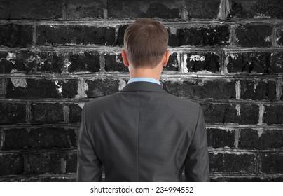 Back view of Businessman looking at brick wall