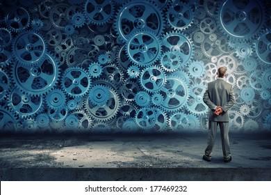 Back view of businessman looking at mechanism of cogwheels