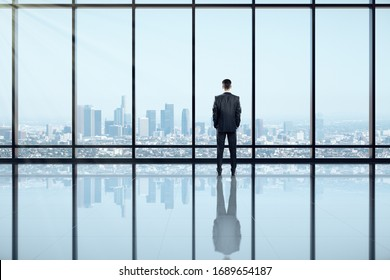 Back view of businessman looking out of window in clean empty office interior with panoramic city view and daylight. Research concept.