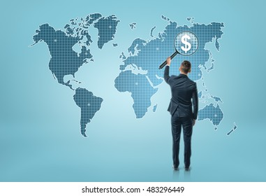 Back view of a businessman looking at world map through magnifying glass and seeing dollar sigh. Global business and communication. International relations.