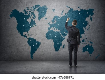 Back view of a businessman making marks on world map. Global communication. International relations. Business staff.