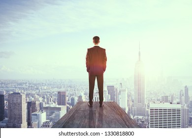 Back view of businessman on rooftop with city view. Success and leadership concept