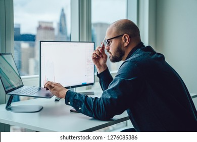 Back view of businessman sitting at office desktop front PC laptop computers with financial graphs and statistics on monitor.Making research, analysis of digital market and investment in block chain