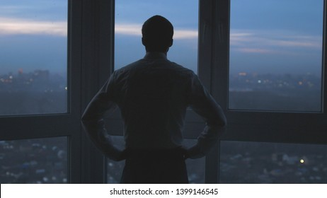Back view of businessman stand near the window and looks on night city background