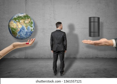 Back view of businessman standing between woman's hand facing up with Earth globe above and man's palm with oil barrel above. Environment. Care or damage. Nature preservation or industry development.
