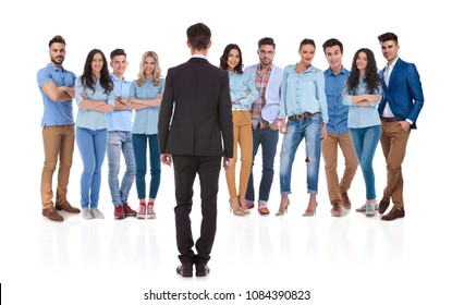 back view of businessman standing in front of his group on white background. He is wearing a black suit and his team blue shirts