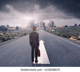 Back view of a businessman standing on road