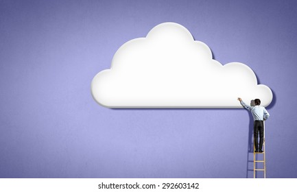 Back view of businessman standing on ladder and reaching to cloud