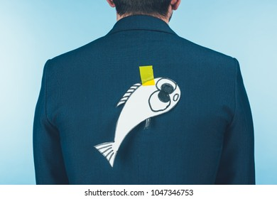 back view of businessman in suit with paper made fish on back, april fools day concept