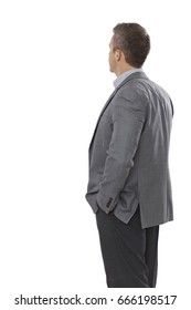 Back view of businessman in suit, standing with hands in pockets.