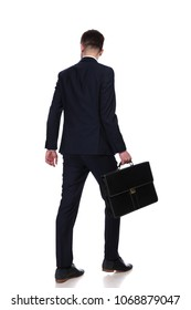back view of businessman with suitcase walking while looking down to side at something. He wears a navy coloured suit, full body picture