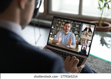 Back view of businessman talk on video call on laptop with multiracial employees or colleagues, male boss have webcam conference or virtual event with diverse businesspeople, use internet on computer