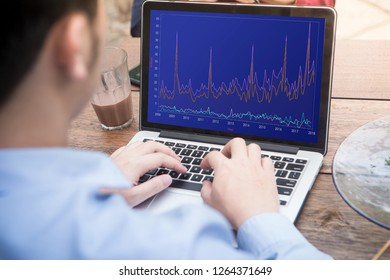 Back view of businessman using laptop with stock chart market on screen.
