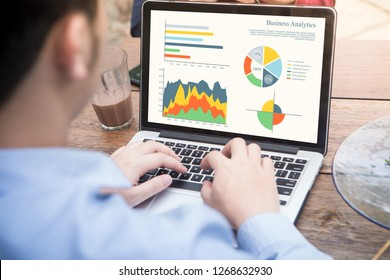 Back view of businessman using laptop analyzing statistics data on laptop screen, working with graphs charts online. Business analysis concept.