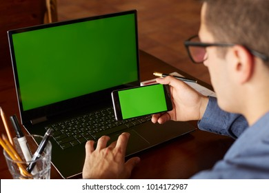 Back view of businessman using smartphone and laptop typing in office. Green screen mockup. Freelancer workspace. People and technology. Copyspace and product placement.