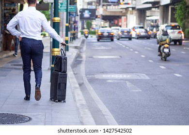 Back view of businessman walking pulling suitcase on the sidewalk. Traffic jam in the city. Lifestyle traveler young man holding baggage on street. Business journey travel. Business concept