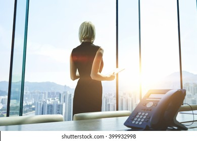 Back view of a businesswoman with digital tablet in hands is watching in office window on a New York city view and thinking about future her company. Female manager is using touch pad during work day