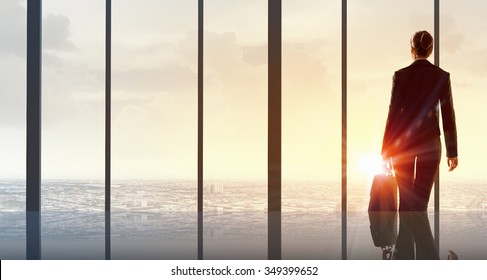 Back view of businesswoman looking on sunrise in office window