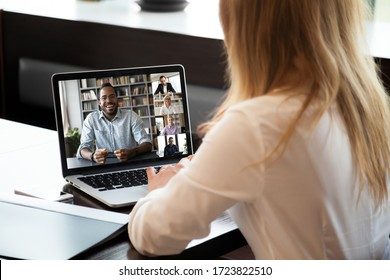 Back view of businesswoman sit at desk talk on video call with multiracial colleagues, woman employee speak have webcam conference on laptop with diverse coworkers, online briefing with team