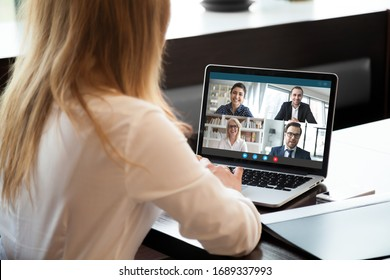 Back view of businesswoman speak using Webcam conference on laptop with diverse colleagues, female employee talk on video call with multiracial coworkers engaged in online briefing from home