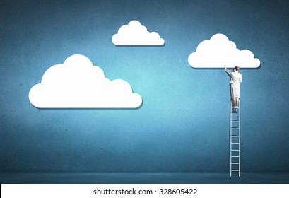 Back view of businesswoman standing on ladder and reaching to cloud