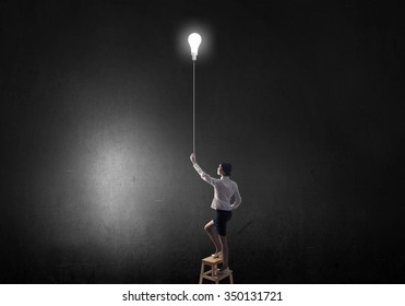 Back view of businesswoman standing on chair and reaching light bulb