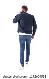 Back view of busy adult man in bomber jacket walking and talking on the cellphone looking away. Full body isolated on white background.