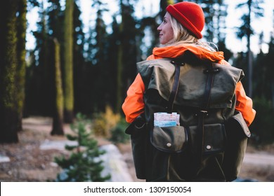Back view of carefree female traveller with touristic rucksack looking aside and smiling during trip to nature environment, positive woman hiker feeling good from spending time in National Park