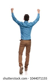 back view of a casual man celebrating success with hands in the air and walking on white background