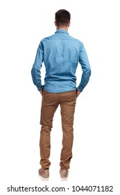 back view of a casual man standing with hands in pockets on white background
