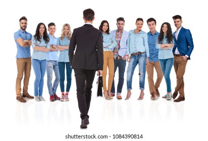 back view of casual team leader with suitcase walking towards his team on white background. He is wearing a black suit and they are wearing blue jeans and shirts, some of them brown pants