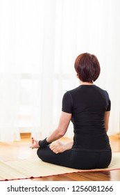 Back View of Caucasian Brunette Woman Practicing Yoga Indoors. Doing Sukhasana Exercises In Physical Lotus Therapy Pose.In Front of Sunny Window in Background..Vertical Shot