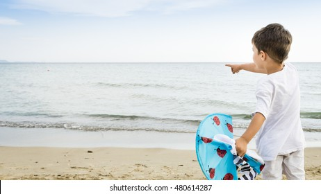 Back view of caucasian child playing with kite on the beach and pointing something