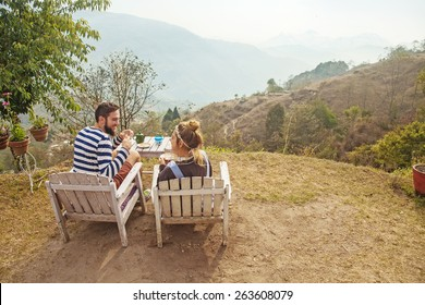 back view of a caucasian couple sitting and having breakfast with a mountain view in Nagarkot, Nepal