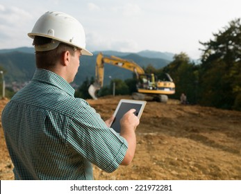 back view of caucasian engineer standing on construction site checking plan on digital tablet