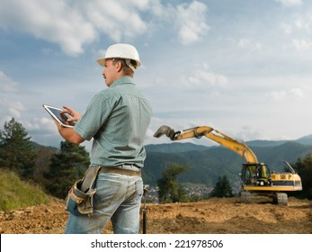 back view of caucasian engineer standing on construction site browsing on digital tablet