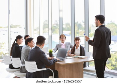 back view caucasian lecturer giving public presentation with company business graph result on white board in meeting room and multiethnic business people are paying attention