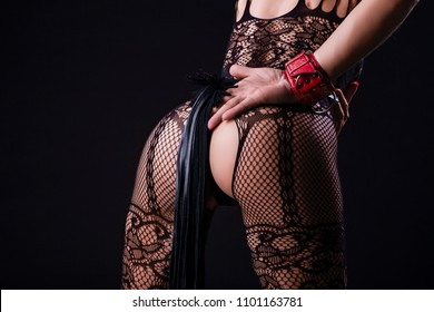 Back View of Caucasian Woman in Sexy Lingerie Posing with Leather Lash for BDSM Role Game.In red Handcuffs. Horizontal Orientation