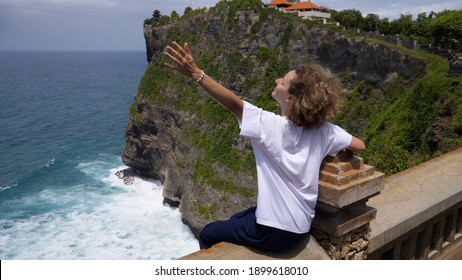 Back view of Caucasian woman sitting on an edge of observation deck with arms spread wide embracing unbelievable beauty of the nature