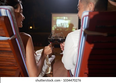 Back view of cheerful Asian couple toasting with wine glasses while sitting on cozy deck chairs and watching movie with help of laser projector, dim territory of resort on background