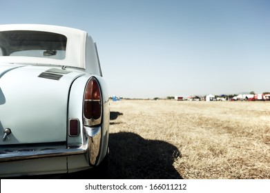Back view of a classic car parked in a field