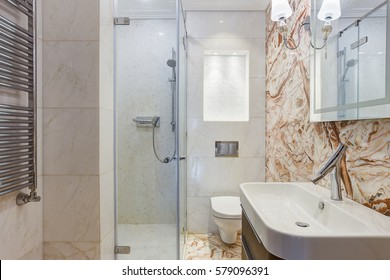 Back view of clear bathroom with element of red and white marble in wall. Shower cabin of glass, sink and mirror on wall. Bowl in corner in the room.