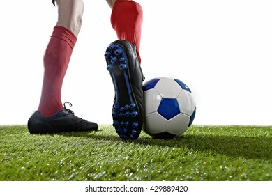 back view close up legs and feet of football player in red socks and black shoes running and dribbling with the ball playing on green grass pitch isolated on white background