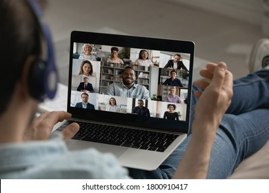 Back view close up of male employee have webcam group digital conference on laptop, engaged in team online meeting, man speak talk on video call on computer from home with diverse colleagues - Shutterstock ID 1800910417