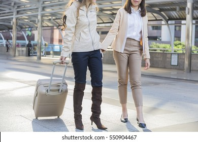 Back view close up of a traveler legs and suitcases in a travel location in a port on holidays,Beautiful Woman happy with suitcase in downtown,Portrait of two women with suitcase