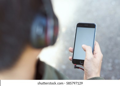 Back view of a close up of Young Man using earphone  mobile smart phone.