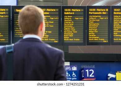 Back view of a commuter checking timetables at Waterloo station in London