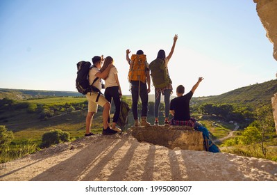 Back view of company of hikers with backpacks celebrating successful achievement while standing with raised arms on hill at sunset during summer adventure