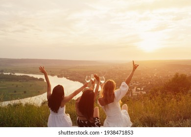 Back view of company of young female friends having fun, drink wine, and enjoy hill landscape and sunset at summer picnic.
